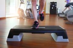 Mujer que hace aeróbicos del paso mientras que en club de salud Foto de archivo