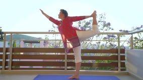 Mujer que hace asana de la yoga en terraza por la mañana almacen de video