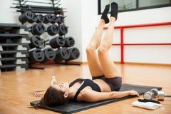 Mujer que hace aumentos de la pierna en el gimnasio imagen de archivo libre de regalías