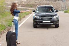 Mujer que hace autostop después de una avería con su coche Imagen de archivo libre de regalías