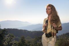 Mujer que hace autostop en una carretera Imagenes de archivo