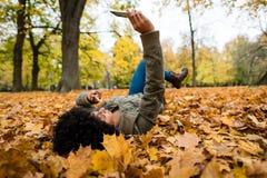 Mujer que hace clic el selfie en un parque del otoño Imagen de archivo