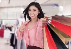Mujer que hace compras con los pulgares para arriba en la alameda foto de archivo