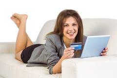 Mujer que hace compras en línea con la tableta y la tarjeta de crédito Imagenes de archivo