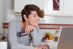 Mujer que hace compras en línea con la tarjeta de crédito Imagen de archivo libre de regalías