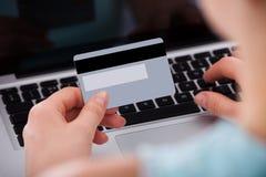 Mujer que hace compras en línea con la tarjeta de crédito y el ordenador portátil Imagen de archivo