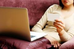 Mujer que hace compras en línea con la tarjeta del crédito en blanco Imagenes de archivo