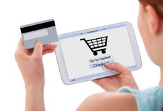 Mujer que hace compras en línea con la tarjeta digital de la tableta y de crédito Fotos de archivo libres de regalías
