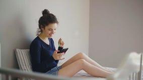 Mujer que hace compras en línea en su cama usando su teléfono y tarjeta de crédito metrajes