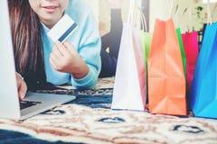 Mujer que hace compras en línea usando la pantalla en blanco del ordenador portátil con la tarjeta de crédito foto de archivo