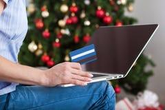 Mujer que hace compras en línea con la tarjeta de crédito para la Navidad Fotografía de archivo libre de regalías