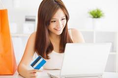 Mujer que hace compras en línea con la tarjeta de crédito y el ordenador portátil Fotos de archivo libres de regalías