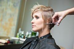 Mujer que hace corte de pelo Imágenes de archivo libres de regalías