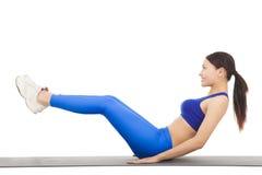 Mujer que hace crujidos abdominales en ejercicio Foto de archivo libre de regalías