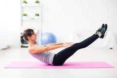 Mujer que hace ejercicio abdominal en la estera en casa Fotografía de archivo libre de regalías