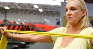 Mujer que hace ejercicio con la banda 4k de la resistencia almacen de video