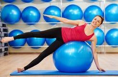 Mujer que hace ejercicio con la bola de la aptitud Fotos de archivo