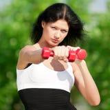 Mujer que hace ejercicio con pesa de gimnasia Fotografía de archivo libre de regalías