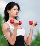 Mujer que hace ejercicio con pesa de gimnasia Foto de archivo