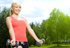 mujer que hace ejercicio con pesa de gimnasia en parque verde Foto de archivo