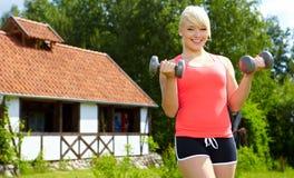 Mujer que hace ejercicio con pesa de gimnasia en parque verde Imágenes de archivo libres de regalías