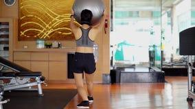 Mujer que hace ejercicio con una bola de los pilates almacen de metraje de vídeo
