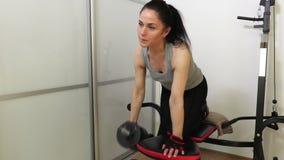 Mujer que hace ejercicio de la aptitud con la pesa de gimnasia para los músculos traseros metrajes