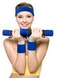 Mujer que hace ejercicio de la aptitud con pesas de gimnasia Fotos de archivo