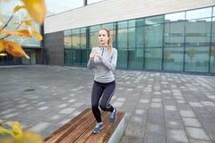 Mujer que hace ejercicio del paso en banco de la calle de la ciudad Imagen de archivo