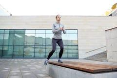 Mujer que hace ejercicio del paso en banco de la calle de la ciudad Fotografía de archivo