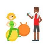 Mujer que hace ejercicio en bola con ayuda del instructor personal, miembro del club de fitness que se resuelve y que ejercita ad Fotografía de archivo libre de regalías