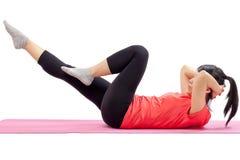 Mujer que hace ejercicios abdominales Fotografía de archivo