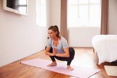 Mujer que hace ejercicios de la aptitud de la yoga en Mat In Bedroom foto de archivo