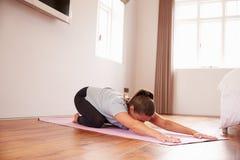Mujer que hace ejercicios de la aptitud de la yoga en Mat In Bedroom imagen de archivo libre de regalías