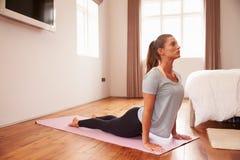 Mujer que hace ejercicios de la aptitud de la yoga en Mat In Bedroom imagenes de archivo