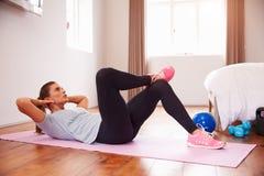 Mujer que hace ejercicios de la aptitud en Mat In Bedroom imagen de archivo