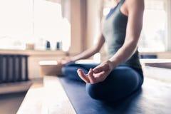 Mujer que hace ejercicios de la yoga en el gimnasio, muchacha de la aptitud del deporte del primer que sienta a Lotus Pose Fotografía de archivo libre de regalías