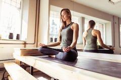 Mujer que hace ejercicios de la yoga en el gimnasio, muchacha de la aptitud del deporte que sienta a Lotus Pose Imagenes de archivo