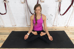 Mujer que hace ejercicios de la yoga en el gimnasio, muchacha de la aptitud del deporte que sienta a Lotus Pose Imágenes de archivo libres de regalías