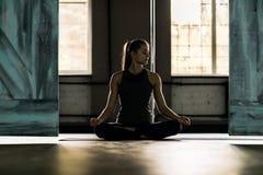 Mujer que hace ejercicios de la yoga en el gimnasio, muchacha de la aptitud del deporte que sienta a Lotus Pose Imagen de archivo
