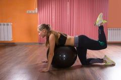 Mujer que hace ejercicios de los pilates en un gimnasio Imagen de archivo