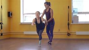 Mujer que hace ejercicios debajo del instructor Supervision almacen de metraje de vídeo