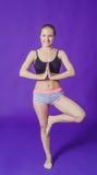 Mujer que hace ejercicios mientras que se coloca en un fondo azul en el cuarto de la aptitud Fotografía de archivo libre de regalías