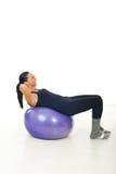 Mujer que hace el ABS en bola de los pilates Fotos de archivo