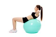 Mujer que hace el ABS en bola del gimnasio fotografía de archivo