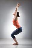 Mujer que hace el asana Utkatasana de la yoga del vinyasa del ashtanga Fotos de archivo