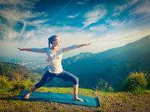 Mujer que hace el asana Virabhadrasana 2 de la yoga - el guerrero presenta al aire libre Fotografía de archivo libre de regalías