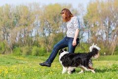 Mujer que hace el baile del perro con un border collie Fotografía de archivo libre de regalías