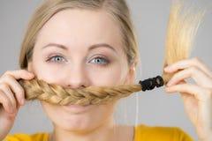 Mujer que hace el bigote fuera del pelo rubio Fotografía de archivo