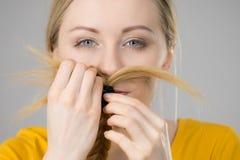 Mujer que hace el bigote fuera del pelo rubio Fotografía de archivo libre de regalías
